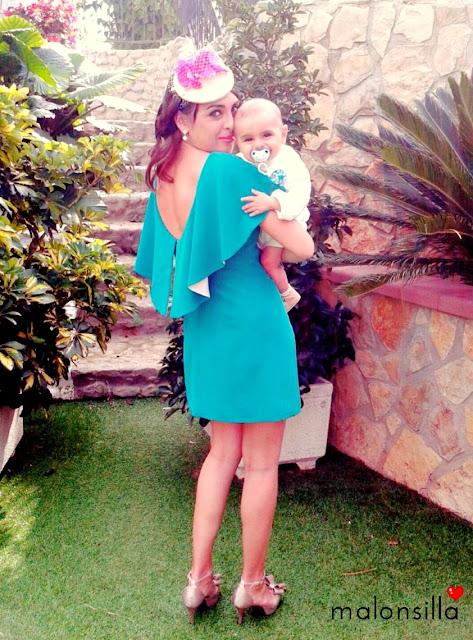 Invitada boda con vestido verde corto de volante y tocado tipo casquete en crudo fucsia con bebé en brazos.