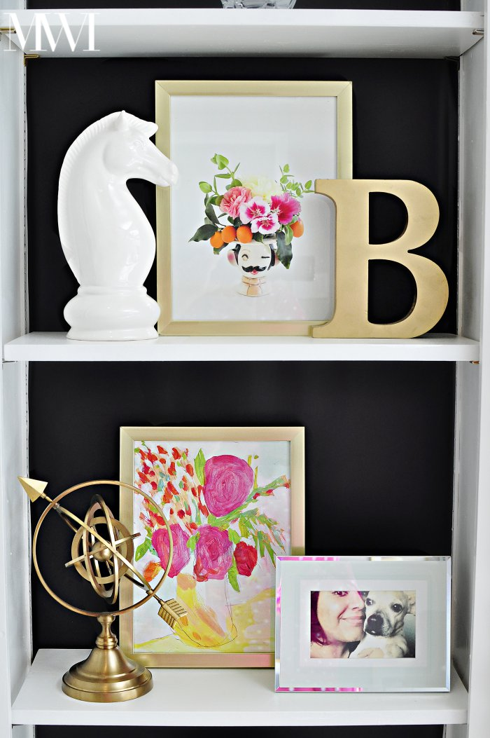A gorgeous black backed bookcase with bold and feminine art with lots of gold touches.