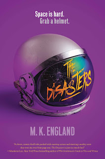 """A white spacesuit helmet with a cracked visor and """"THE DISASTERS"""" scrawled on it in bright yellow, placed against a purple background."""