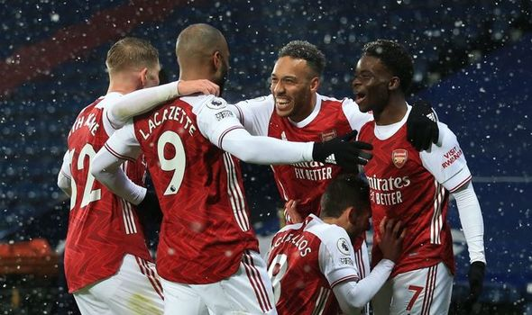 Arsenal players celebrating goal in snowy condition at the Hawthorns