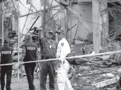 Para petugas kepolisian sedang melakukan penyelidikan di lokasi peledakan bom di Jl. Legian, Kuta, Bali. Peristiwanya terjadi pada tanggal 12 Oktober 2002.