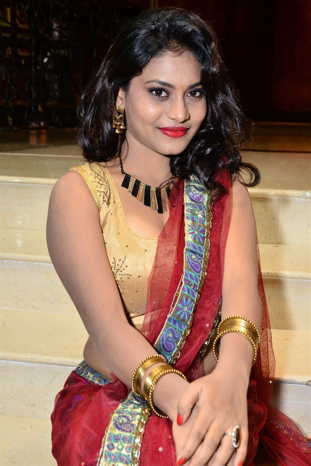 Priya Augustin Looks Stunning in Sleeveless Choli and Red Saree