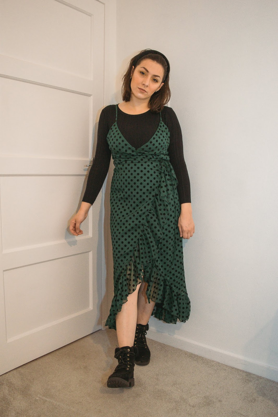 I am standing against a white background and I am wearing a black ribbed long sleeve top under a green frill polka dot dress that is a mid length. I am wearing black boots with fluffy trim.