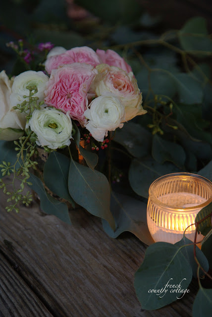Flowers and candles with eucalyptus on table