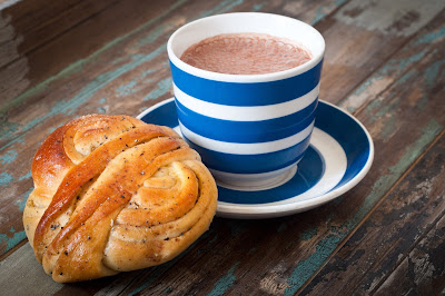 Pic of a Swedish bun and coffee in cup on table top