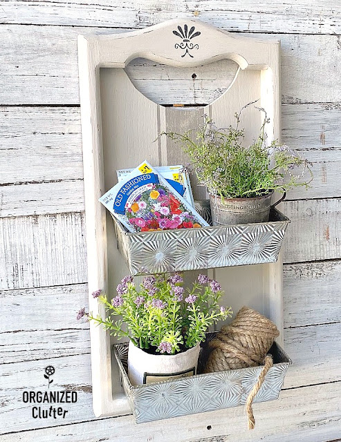 Photo of wall bins made from a wooden calendar holder and loaf pans.