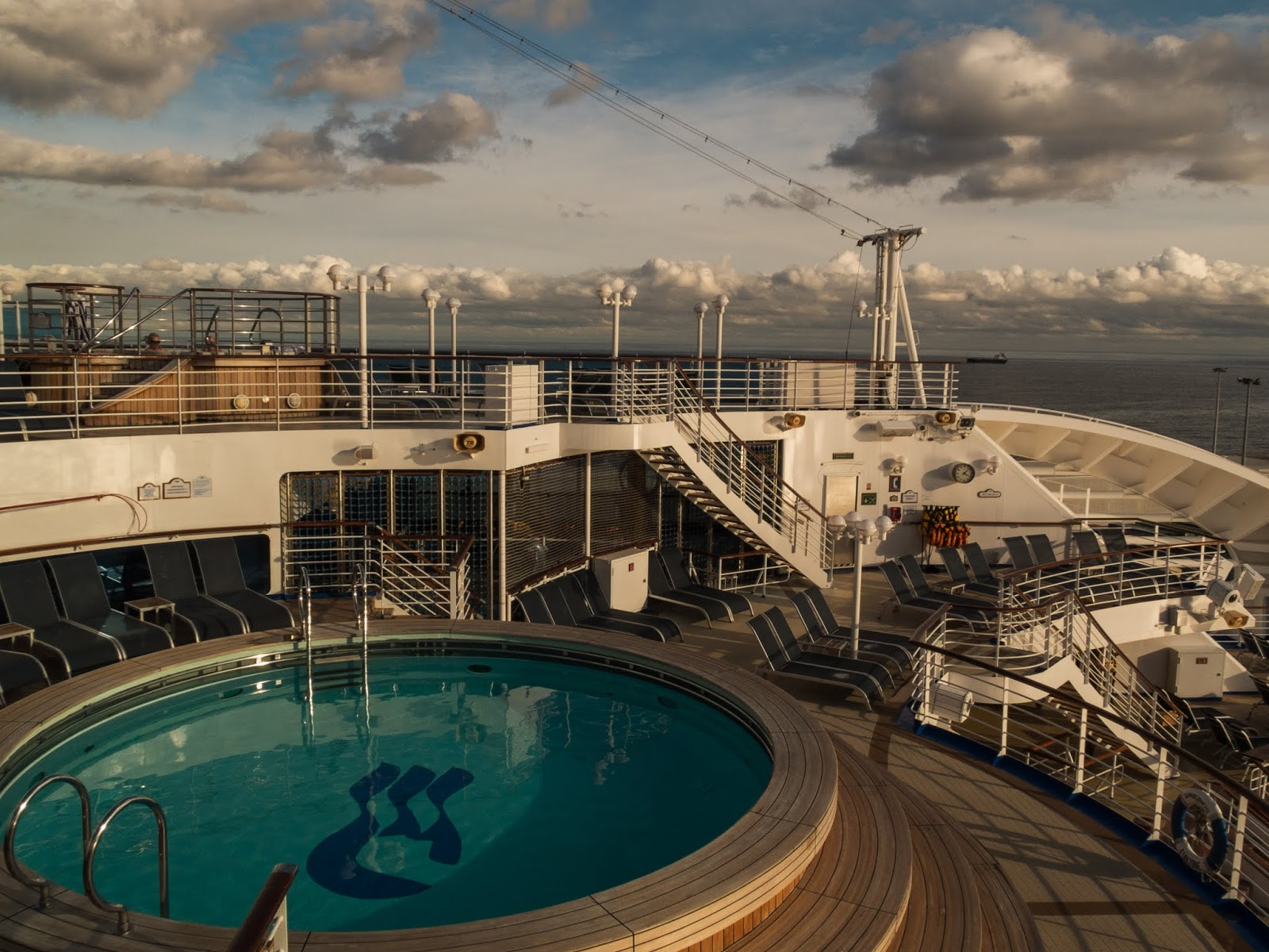 A round pool on a cruise ship on a sunny day.