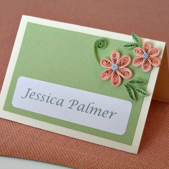 two quilled flowers with leaves on a place card on a table