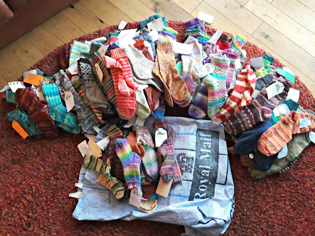A photo of a large pile of socks arranged in a rainbow shape on a red rug.  The socks are sorted by size from small on the left to large on the right.  They are knitted in many different colours and patterns.  In the centre is a grey Royal Mail sack with a pile of children's socks sitting on it.  On the top is a small pair of socks knitting in West Yorkshire Spinners Winwick Mum yarn in shade Wildflower