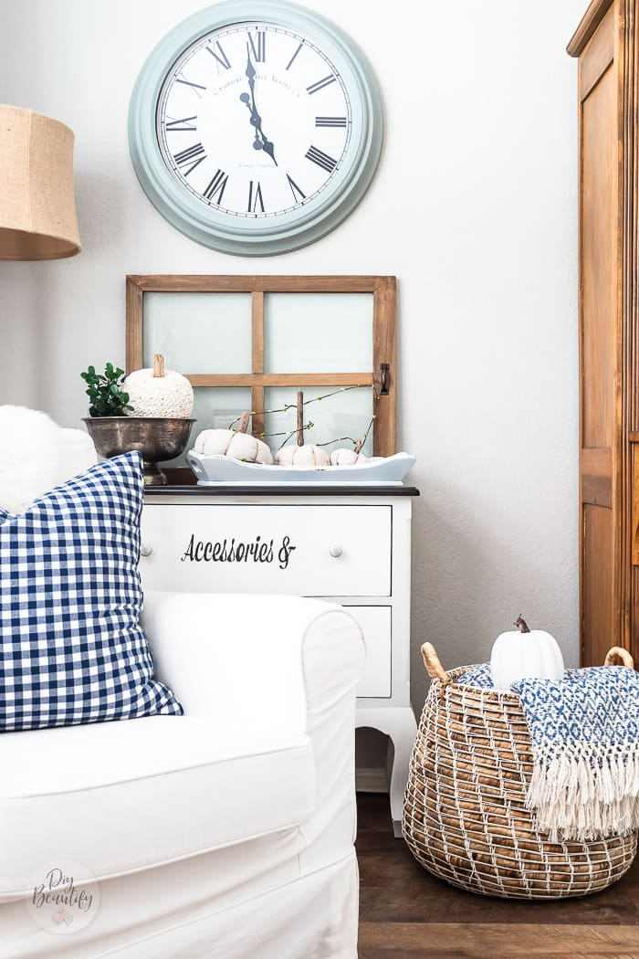 blue gingham pillow on white chair, basket with blue throw and white pumpkin, vintage window and blue clock