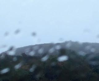 Steep hill top viewed through wet window