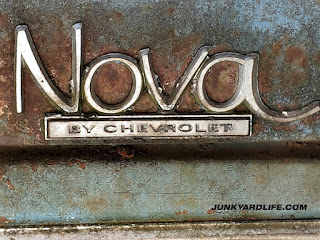 "1970 Chevy ""Nova"" emblem with rust and blue paint around the chrome emblem."