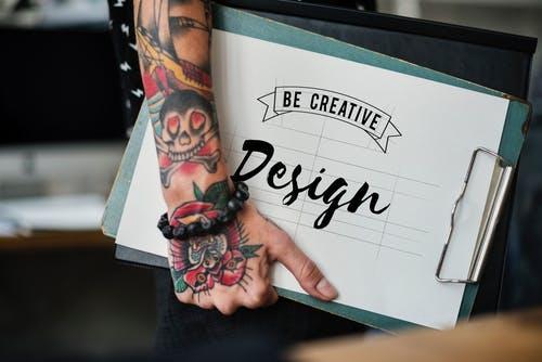 Brazo tatuado con carpeta de creación: sé creativo: diseña