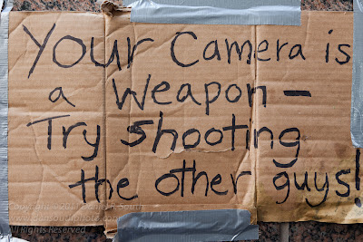 a photo of an occupy wall street sign that says your camera is a weapon