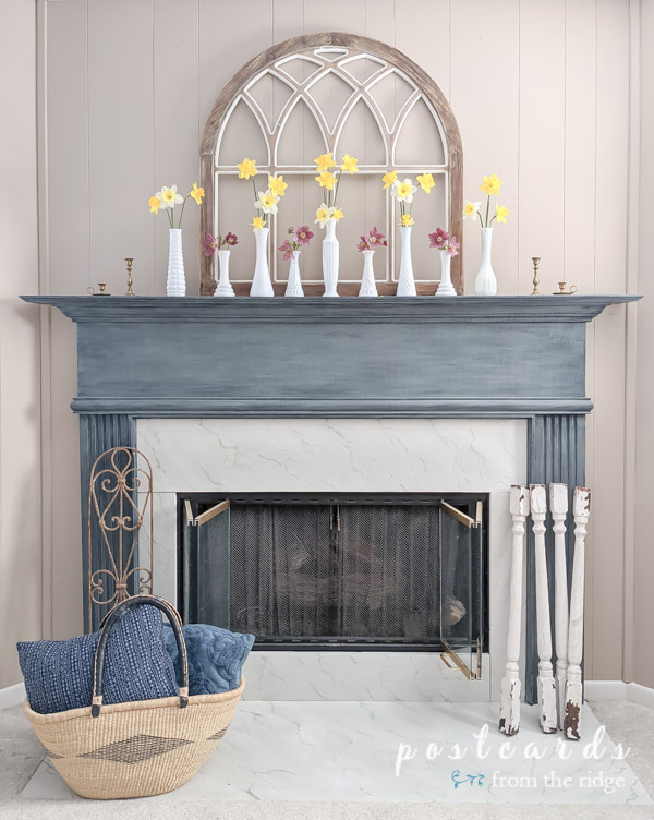 blue fireplace mantel with yellow daffodils in vintage white milk glass vases