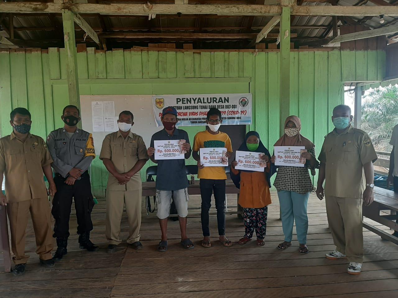 Pastikan Keamanan, Bhabinkamtibmas Polsek Manuhing Kawal Pembagian BLT-DD di Desa Binaannya