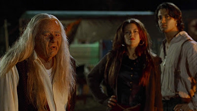 Movie still for the 1996 horror film Thinner where Michael Constantine, Kari Wuhrer, and Terence Kava confront Robert John Burke at their campsite