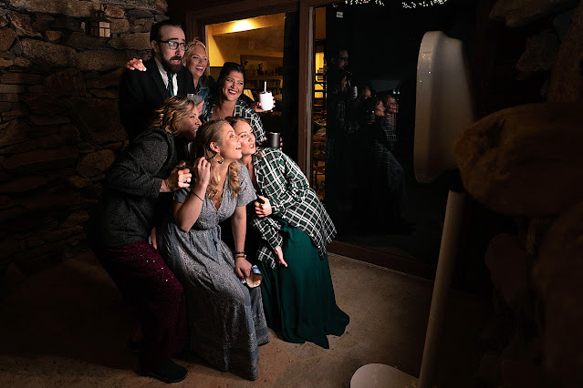 Wedding attendees taking nighttime pictures in front of rustic stone wall Magnolia Farm Asheville Wedding Photography captured by Houghton Photography