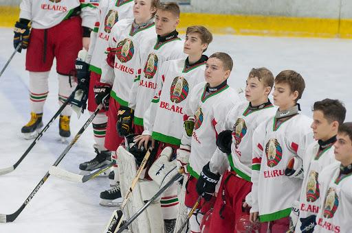 Pusaudži hokeja formās stāv uz ledus