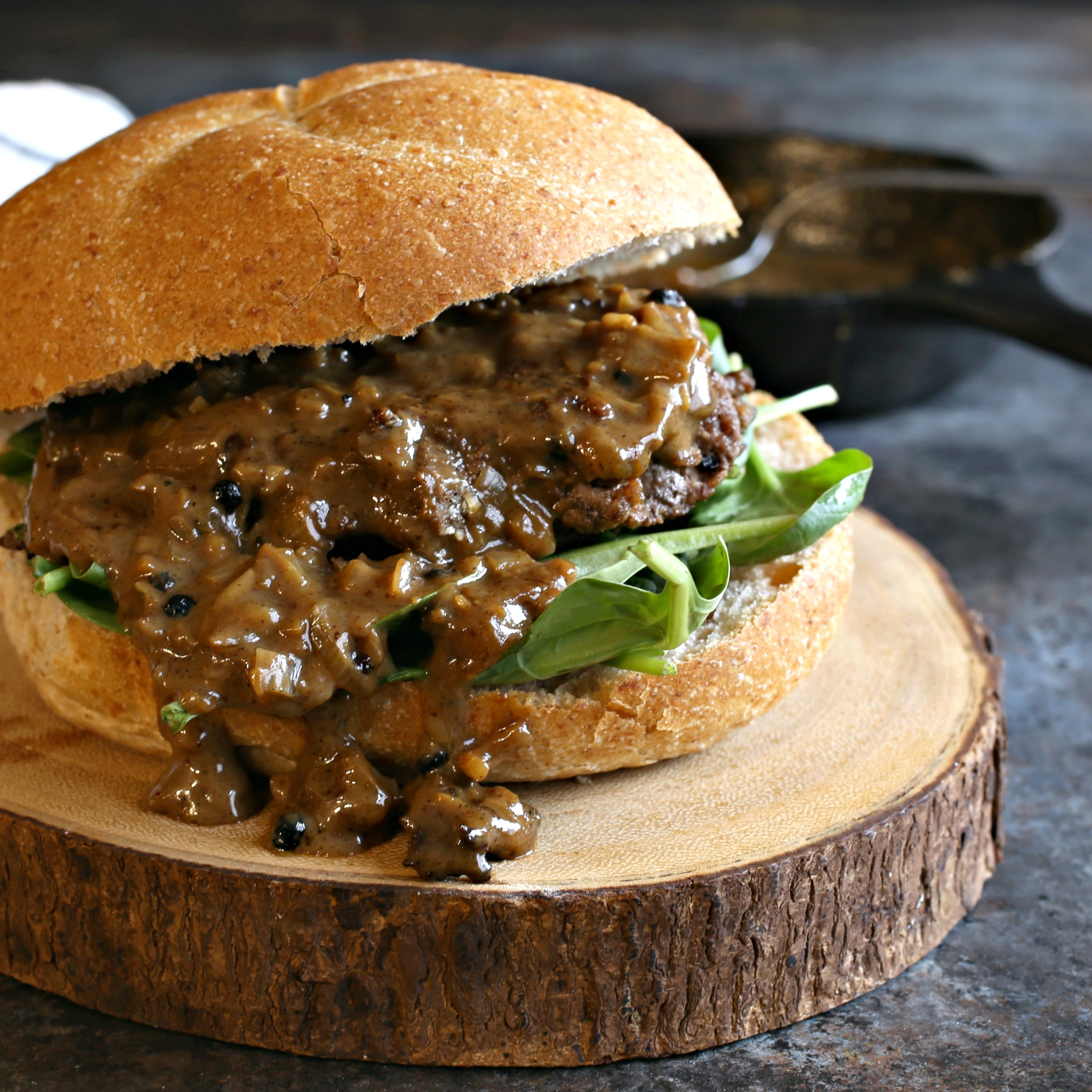Recipe for hamburgers cooked with a creamy au poivre peppercorn sauce.