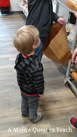 child watching older brother pick out rolls for dinner