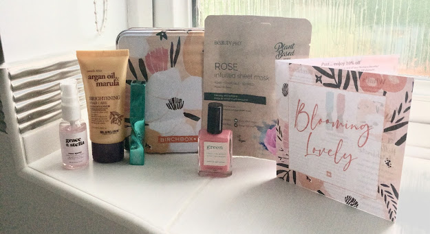 A metal tin with a floral pattern on. In front of the tine are beauty products including a spray bottle with a pink liquid in, a tube of hair conditioner, a turquoise mascara, a bottle of pink nail polish, a face mask packet and a paper booklet with 'Blooming Lovely' written on the front.