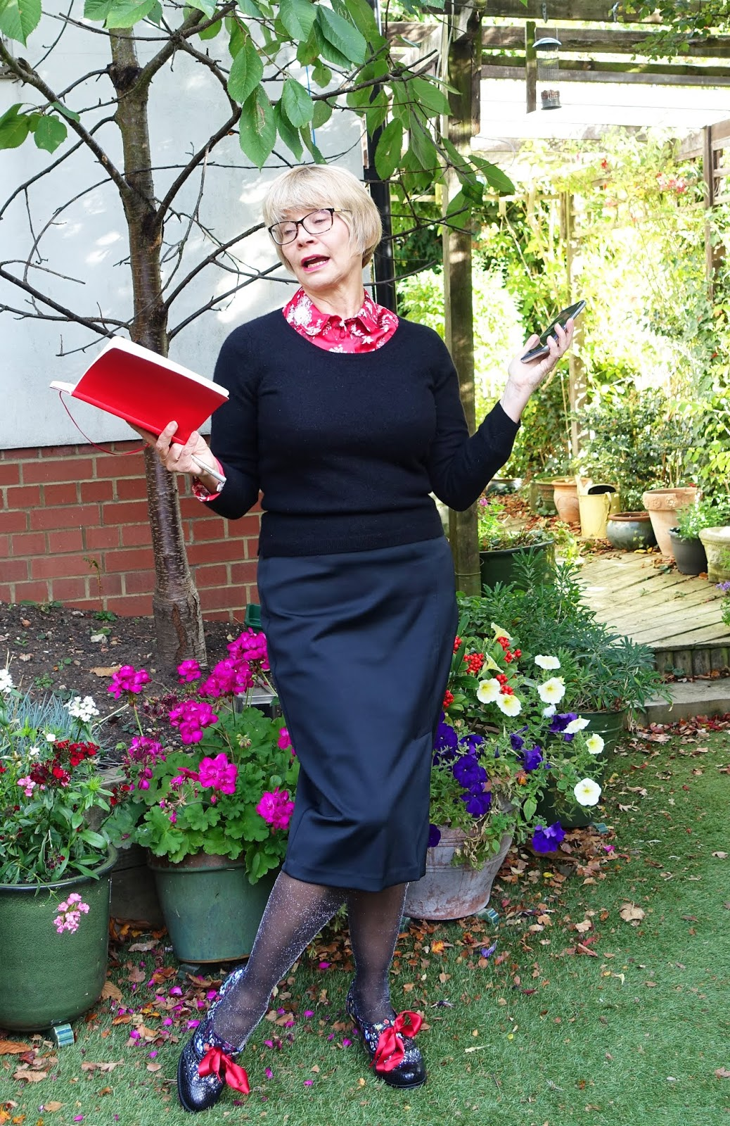 Over 45s blogger Gail Hanlon in black skirt and jumper, red and white floral blouse, sparkly tights and statement shoes