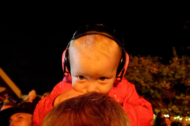 Little with ear defenders on leaning on her Daddy's head while sitting on his shoulders