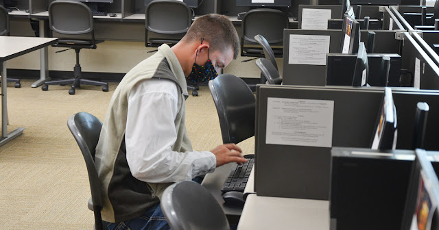 student sitting at computer inside the library