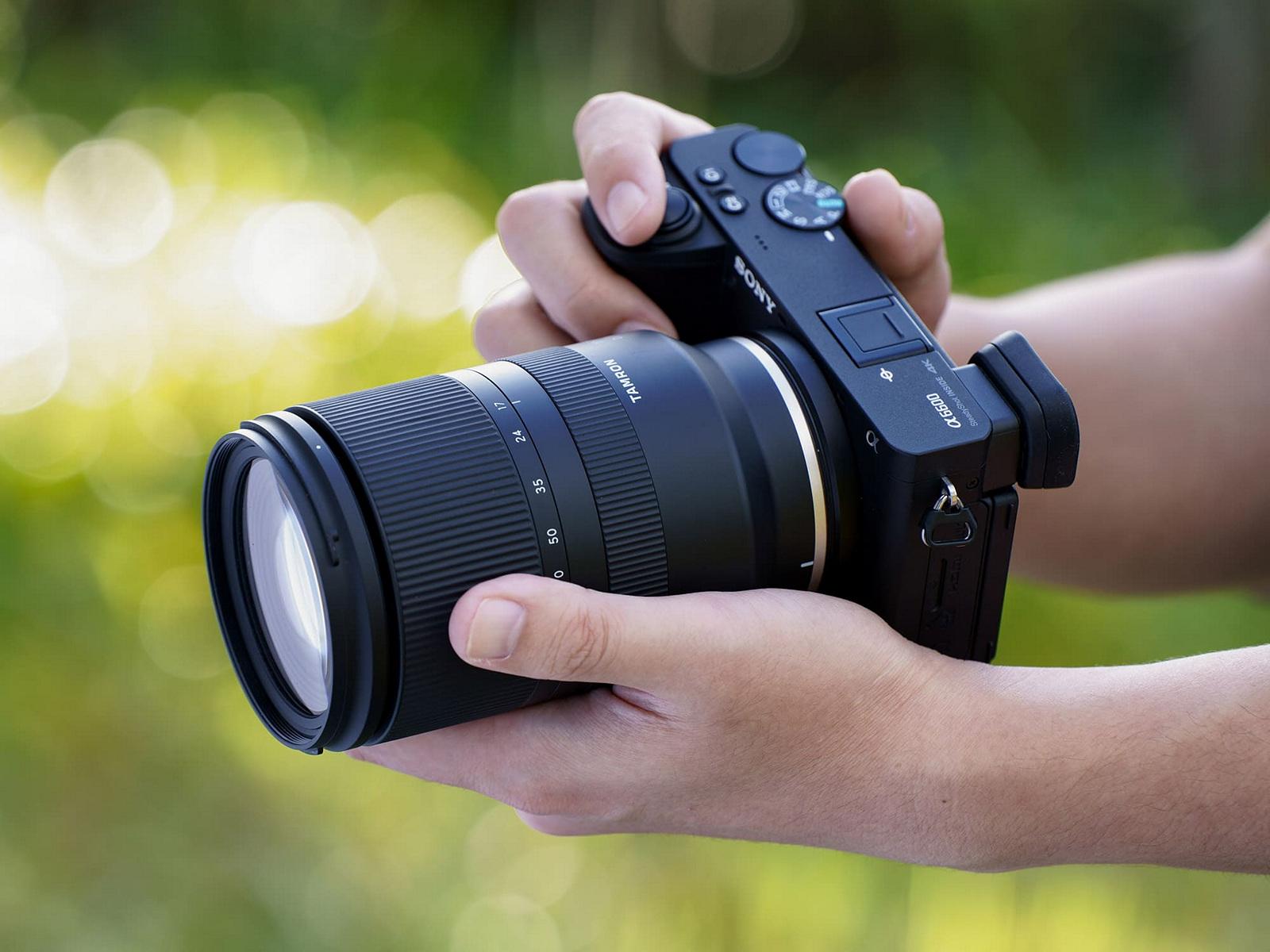 Tamron 17-70mm f/2.8 Di III-A VC RXD с камерой Sony A6600 в руках фотографа