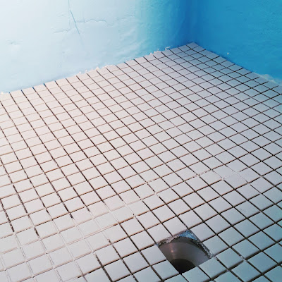 Shower floor with new small square white tiles and walls covered with blue waterproofing membrane.