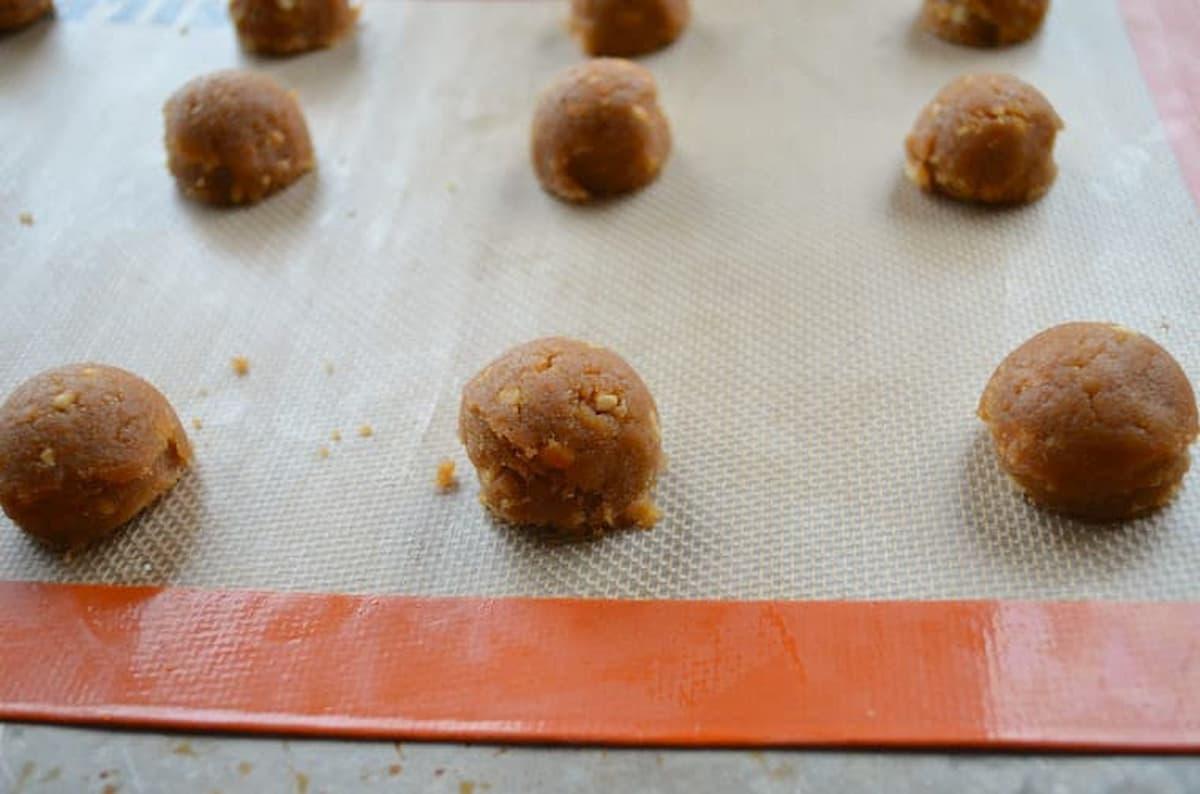 Balls of Flourless Peanut Butter Cookie dough on a silpat lined baking sheet.