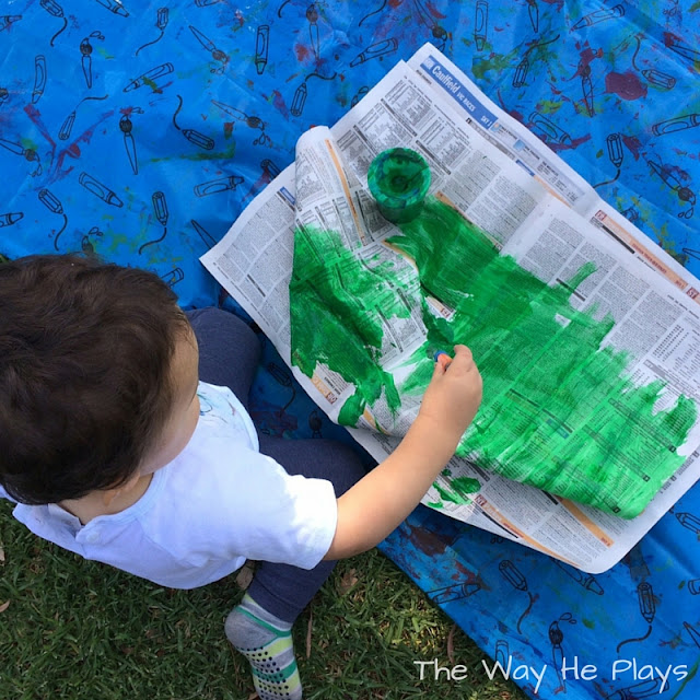 Toddler painting with green paint on newspaper