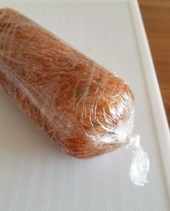 Fiambre de pollo envuelto en papel film, antes de cocinar