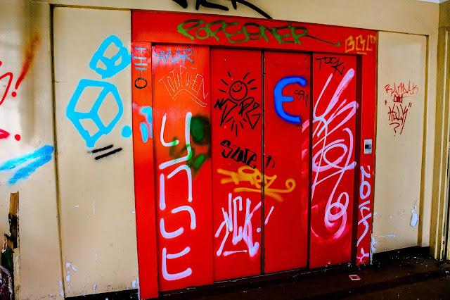 photo de l'ascenseur rouge du sanatorium tagué qui ne marche plus
