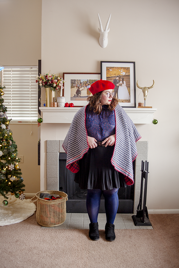An outfit consisting of a red beret, a blue collared blouse with a red heart print, a white and blue houndstooth shawl, a black pleated knee lenth skirt, navy tights and black ankle boots.