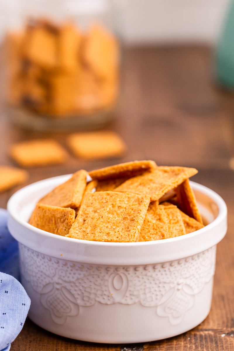 Photo of Keto Smoked Cheddar Crackers (Cheez-Its) in a white bowl on a wooden table.