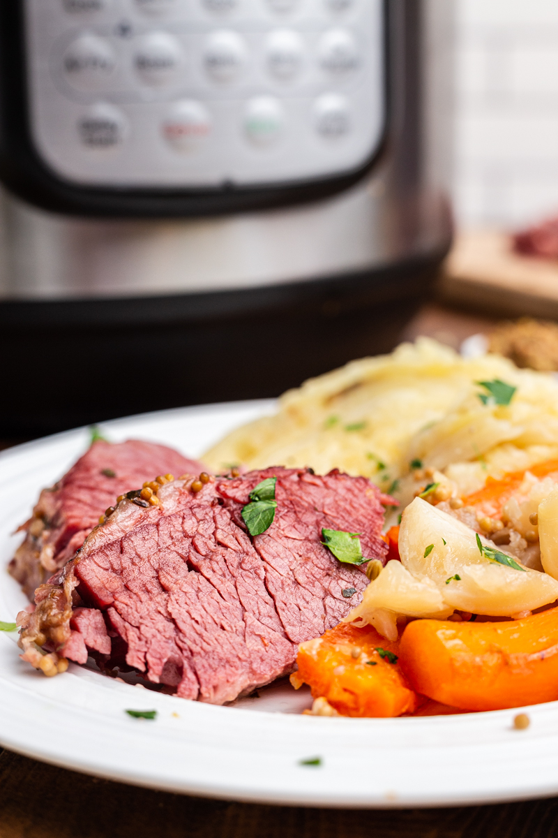 Photo of keto corned beef and cabbage with turnips and carrots on a white plate with an Instant Pot in the background.
