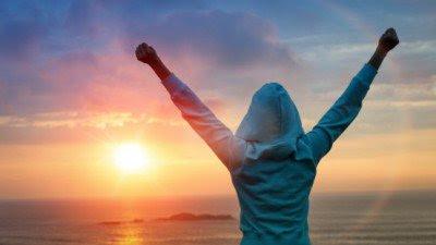 Mujer levantando los brazos al atardecer