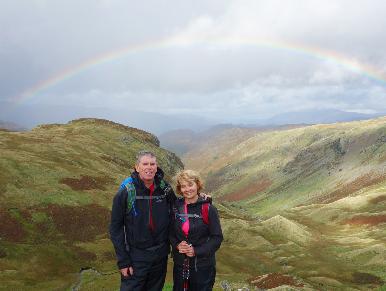 Active middle aged couple on walking holiday under a rainbow in the Lake District