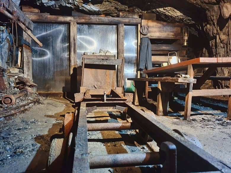 A picture containing wooden, chair, old, wood, inside the gold mine