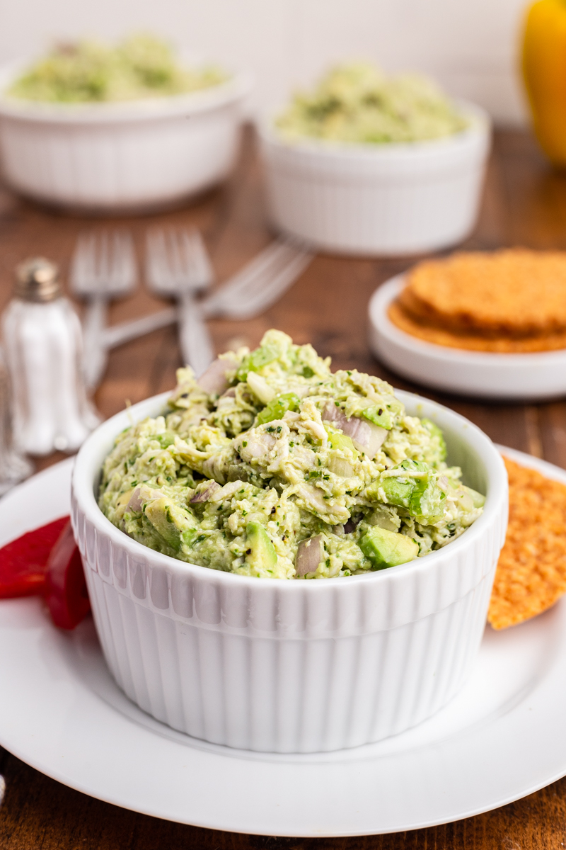 Photo of Keto Avocado Ranch Chicken Salad in a white bowl on a wooden table with crackers and additional bowl of chicken salad in the background.