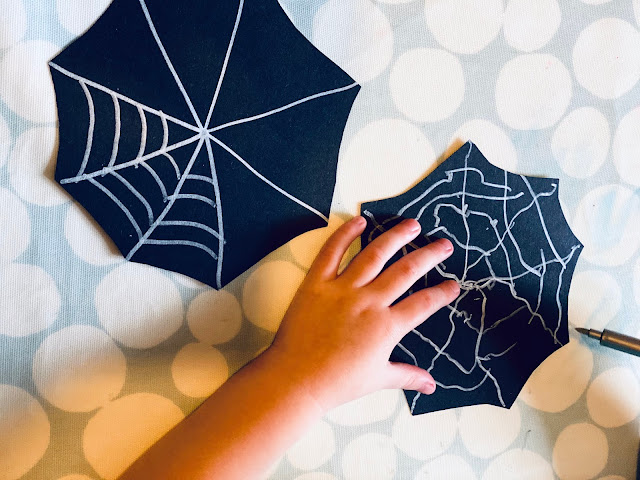 A 3 year old using a silver metallic craft pen to draw a spiders web on to black card