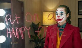 """Joker mirándose al espejo, serio, y pone """"put on a Happy face"""""""