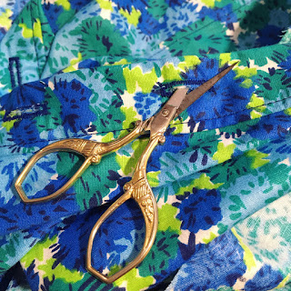 A pair of sharp gold scissors cutting a buttonhole in blue and green floral fabric.