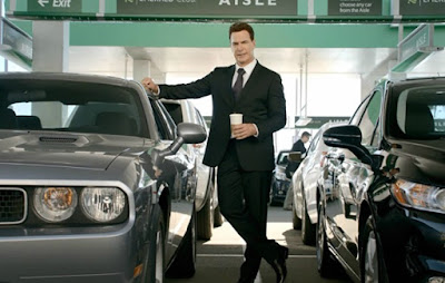 Patrick Warburton posing with car & drinks in his hand