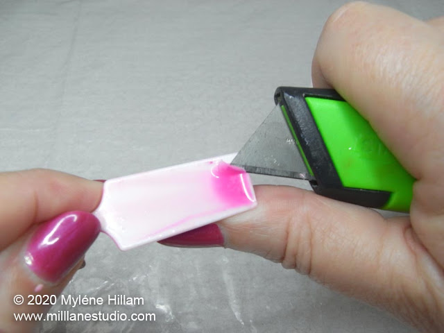 Using a utility knife to lift the edge of cured resin from a plastic spatula