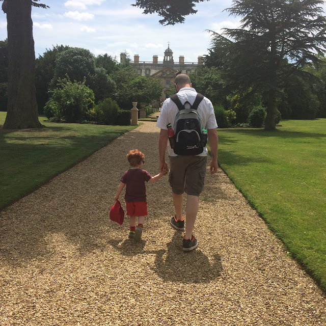 Daddy and son walking hand in hand on a gravel path in stately gardens