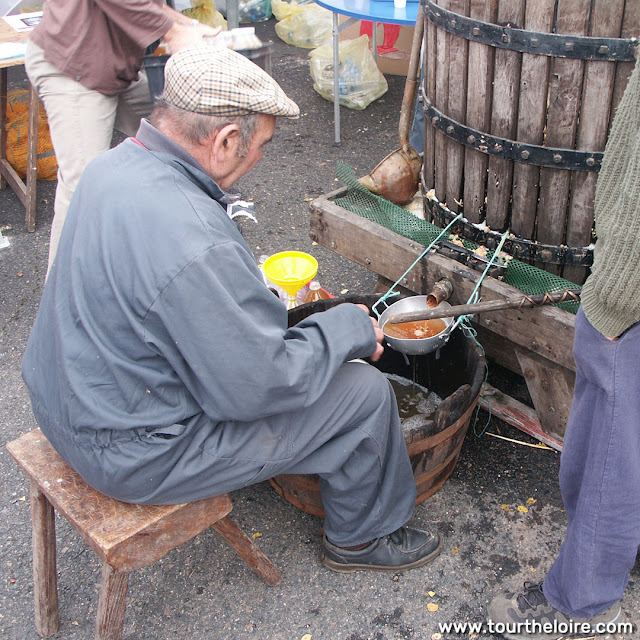 Pressing apples into juice at a fair, Indre et Loire, France. Photo by Loire Valley Time Travel.