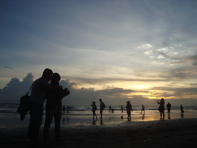 a sunset on a beach with people watching it